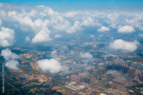 aerial view, flying above the puffy white clouds and over ground landscape in China, Asia. - 223951053