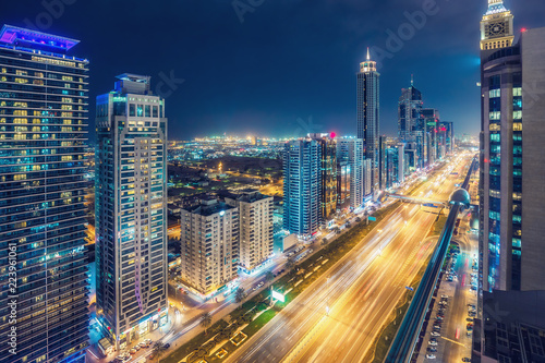 Aerial view on downtown Dubai, UAE with highways and skyscrapers. Scenic nighttime skyline.