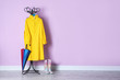 Leinwanddruck Bild - Umbrella, raincoat and gumboots near color wall with space for design