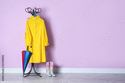 Leinwanddruck Bild Umbrella, raincoat and gumboots near color wall with space for design