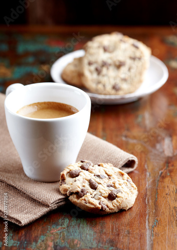 Leinwandbild Motiv Cup of coffee and chocolate chip cookies. Symbolic image. Concept for a tasty snack. Sweet dessert. Rustic wooden background. Selective focus. Close up.