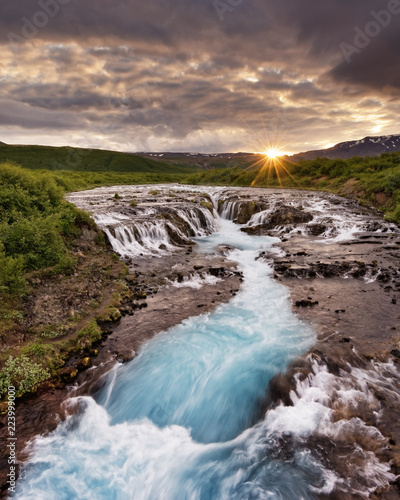 Large waterfall in a wide landscape with evening light, sunset with rays on a mountain range, water movement in long exposure - Location: Iceland, Golden circle, Bruarfoss - 223999000