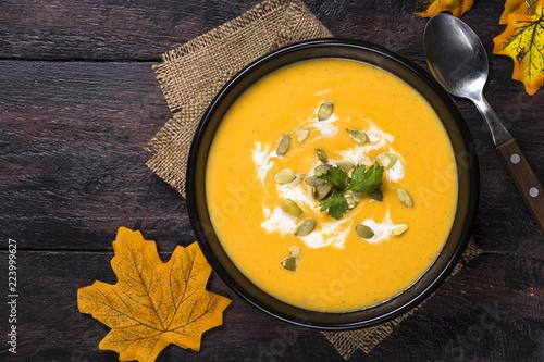 Pumpkin cream soup on dark wooden table. © nadianb
