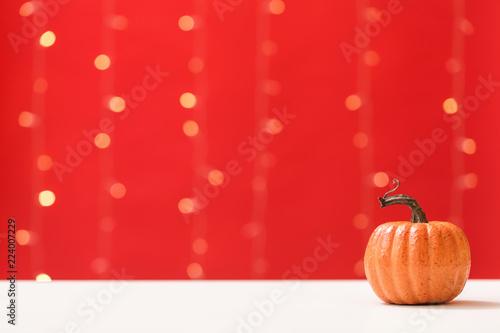 A autumn pumpkin on a shiny light red background - 224007229