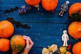 Halloween symbols. Pumpkins and cute figures of halloween evils. Bats. Blue wooden background top view copy space