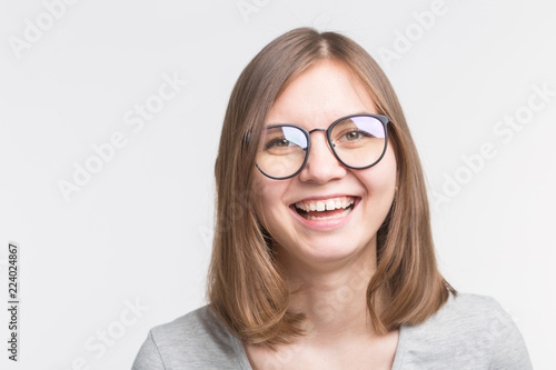 Portrait of laughing happy brown hair girl in a glasses over white background © satura_