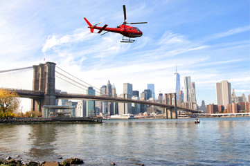 Helicopter flying over New York City skyscrapers and Brooklyn Bridge, USA