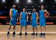 four basketball players standing on basketball court