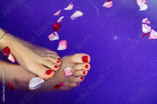 Leinwanddruck Bild Pretty woman feet with red nails pedicure toes enjoying the healing benefits of hot bath soak, flower petals floats on deep blue violet water background with little pieces of bathing pearls and salt
