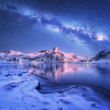 Leinwandbild Motiv Milky Way above frozen sea coast and snow covered mountains in winter at night in Lofoten Islands, Norway. Arctic landscape with blue starry sky,  water, ice, snowy rocks, milky way. Beautiful space