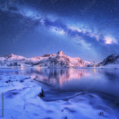 Leinwanddruck Bild Milky Way above frozen sea coast and snow covered mountains in winter at night in Lofoten Islands, Norway. Arctic landscape with blue starry sky,  water, ice, snowy rocks, milky way. Beautiful space