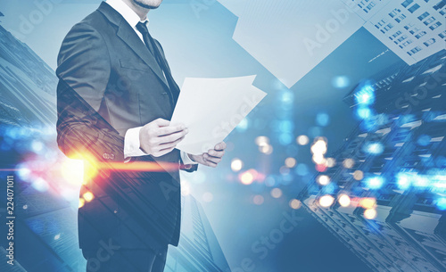 Leinwanddruck Bild Businessman with papers, night cityscape