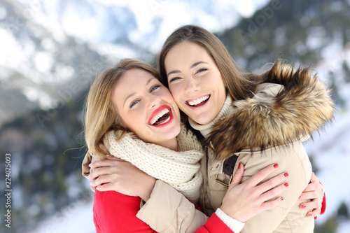 Happy friends cuddling and posing in winter holiday - 224075093