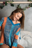 A beautiful woman lying on a bed in a modern apartment and wearing a colourful sweater. - 224097863