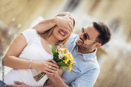 Picture of young man surprising woman with flowers - 224100075