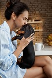 Woman loving and kissing cute dachshund puppy