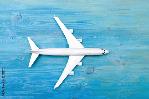 Toy airplane isolated on blue wooden table surface background. Air transportation concept.