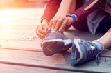 Runner tying her sport shoes - 224113669