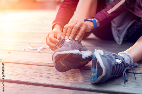 Runner tying her sport shoes - 224113669
