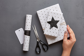 Flat lay Christmas concept with gift boxes and decoration in black and white colors. Gift wrapping. Top view