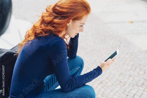 rothaarige frau sitzt draußen auf einer treppe und schaut auf ihr mobiltelefon