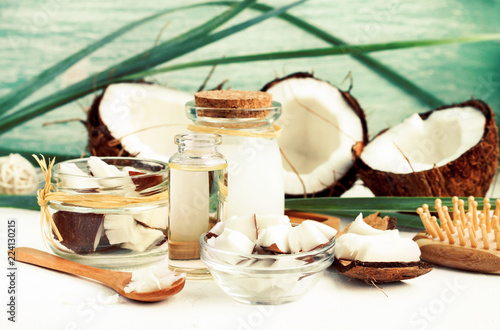 Fresh coconut pulp pieces in jars, coconut oil bottles, homemade nut milk, organic cosmetic beauty products for hair and body care.  - 224130215