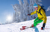 Skier skiing downhill in high mountains against blue sky - 224131669