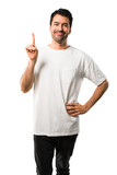 Young man with white shirt showing and lifting a finger in sign of the best on isolated white background - 224135878
