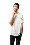 Young man with white shirt showing and lifting a finger in sign of the best on isolated white background - 224135879
