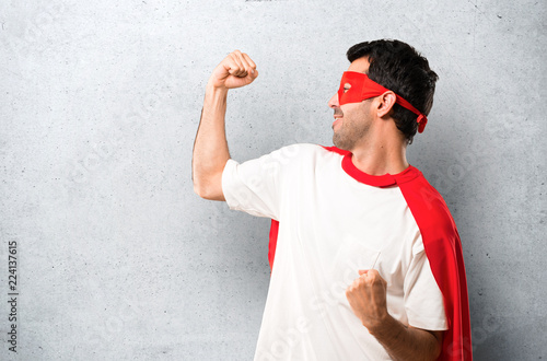 Leinwandbild Motiv Superhero man with mask and red cape celebrating a victory in winner position on textured grey background
