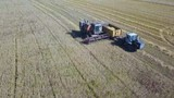 The combine will unload the grain into the truck. Aerial view. - 224143282