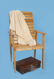 chaise longue and a suitcase on a blue background, a composition about a rest - 224152854
