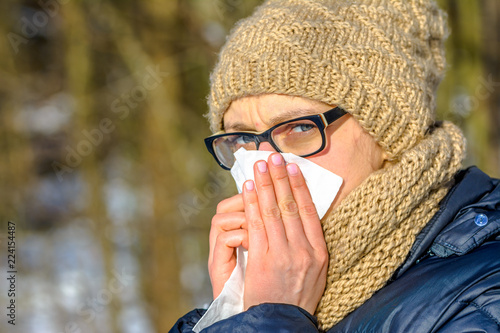 Foto Murales Sneezing woman blowing her nose with a tissue. Sick woman with cold and flu in winter, outdoors. Girl in warm clothes - hat and scarf