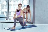 Inner energy. Beautiful mature woman doing asana while trainer correcting her pose