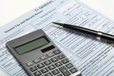 Calculator and pen on top of tax forms - 224158027