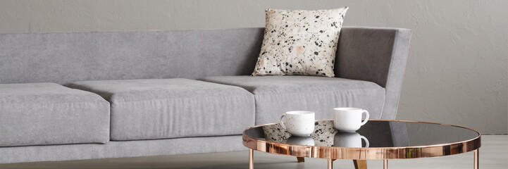 Real photo with close-up of two coffee cups placed on rose gold end table in room interior with grey sofa with lastrico cushion © Photographee.eu