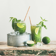 Green matcha ice-tea with lime and mint in glasses over rustic cupboard, white wall at background, copy space, square crop. Vegan, vegetarian, healthy summer refreshing drink