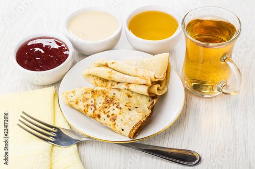 Folded pancakes, jam, honey, condensed milk, fork, cup of tea © Evgeny