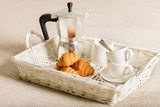 Breakfast in bed. On a white wicker tray there is a coffee maker, coffee white cups and croissants.