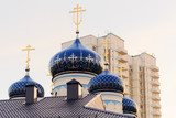 Domes of the Orthodox Church with golden crosses against the background of a multi-storey house and sky