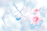 Blue butterfly in the snow on pink roses in a fairy garden. Artistic Christmas image. Delicate gentle pink and blue tone.