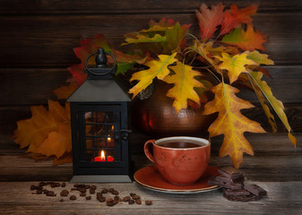 Cozy autumn background with yellow leaves, lantern, hot coffee cup coffee beans and chocolate on wooden background with copy space