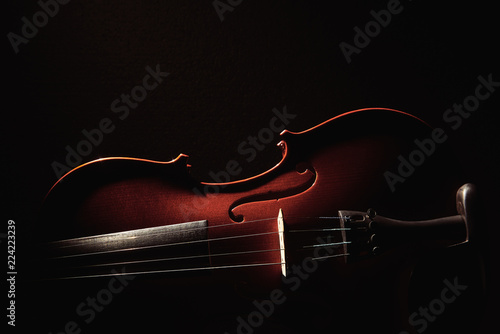 part of a violin on a black background with hard light - 224223239