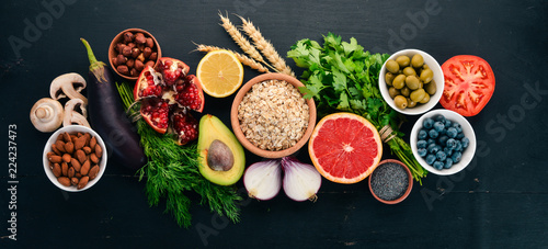 Foto Murales Healthy food clean eating selection: Vegetables, fruits, nuts, berries and mushrooms, parsley, spices. On a black background. Free space for text.