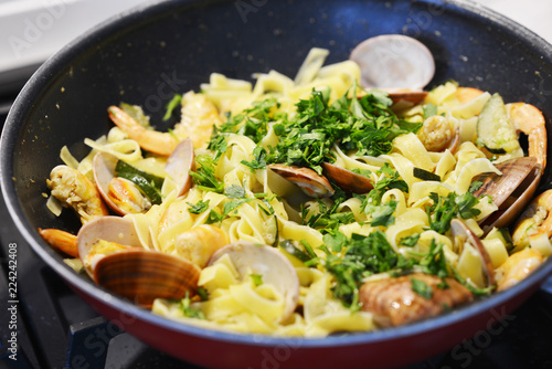 Fototapeta Appetizing seafood pasta with vongole and fried shrimps in a pan