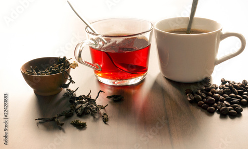 Coffee and tea with coffee bean and tea leaves on wooden floor.