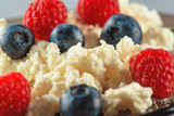 Cottage cheese with fresh raspberries and blueberries for a healthy breakfast with ripe berries. Background is a natural healthy product.
