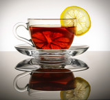 A glass cup of tea with the lemon stands on the reflecting surface