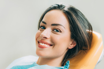 Beautiful female patient sitting in dentist chair