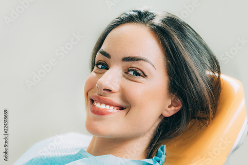 Beautiful female patient sitting in dentist chair - 224318669